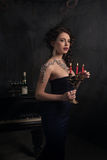 Beautiful young woman in black dress next to a piano with candelabra candles and wine, dark dramatic atmosphere of the castle. Boh. Emia royalty free stock photography