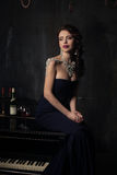 Beautiful young woman in black dress next to a piano with candelabra candles and wine, dark dramatic atmosphere of the castle. Boh. Emia stock image