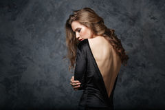Beautiful young woman in black dress with open back Stock Photography