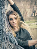 Beautiful young woman in black dress outdoor. Portrait of attractive blonde young woman in black dress, outdoor looking at camera, playing with scarf or foulard Royalty Free Stock Photo