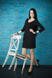 Beautiful young woman in a black dress posing against the backdrop of a blue brick wall Stock Photography