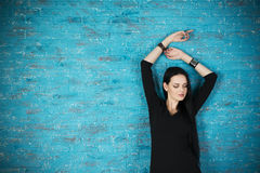 Beautiful young woman in a black dress posing against the backdrop of a blue brick wall Stock Images