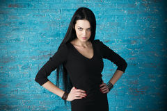 Beautiful young woman in a black dress posing against the backdrop of a blue brick wall Royalty Free Stock Photo