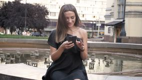 Beautiful young woman in black dress sitting in park and using smartphone. Beautiful woman in black dress sitting in park and using smartphone stock footage