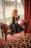 Beautiful young woman in black fashion dress with open back sitt Stock Photo