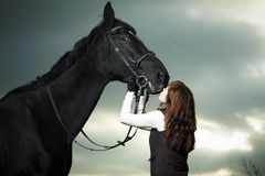 Beautiful young woman with a black horse Stock Photos