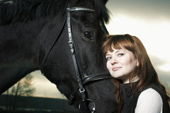 Beautiful young woman with a black horse Royalty Free Stock Photo