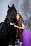 Beautiful young woman with a black horse Stock Images