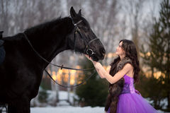 Beautiful young woman with a black horse Royalty Free Stock Images