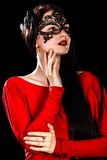 Beautiful young woman in a black mask and a red dress Royalty Free Stock Photos