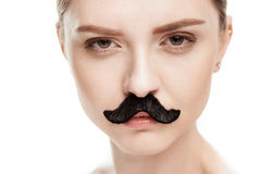 Beautiful young woman with black mustaches looking at camera. Isolated on white stock photography