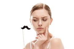 Beautiful young woman with black mustaches on stick. Isolated on white stock images