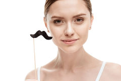 Beautiful young woman with black mustaches on stick. Isolated on white stock image