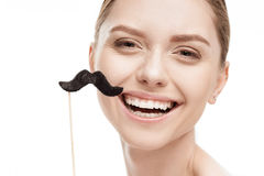 Beautiful young woman with black mustaches on stick. Isolated on white stock photography