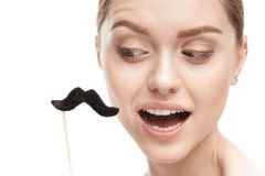Beautiful young woman with black mustaches on stick. Isolated on white royalty free stock image