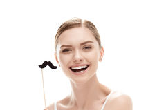 Beautiful young woman with black mustaches on stick. Isolated on white royalty free stock photos