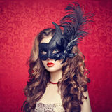 Beautiful young woman in black mysterious  Venetian mask Royalty Free Stock Images