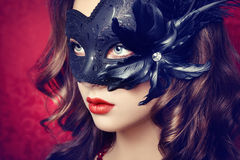 Beautiful young woman in black mysterious  Venetian mask Royalty Free Stock Photo
