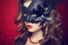 Beautiful young woman in black mysterious  Venetian mask Royalty Free Stock Image