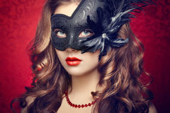 Beautiful young woman in black mysterious  Venetian mask Stock Photo