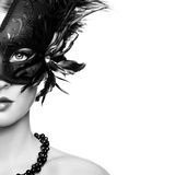 Beautiful young woman in black mysterious venetian mask stock image