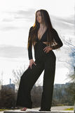 Beautiful young woman. Young woman with black overalls posing outdoor Royalty Free Stock Photography