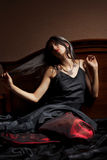 Beautiful young woman in black and red dress sitti Royalty Free Stock Images