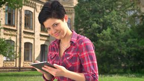 Beautiful young woman with black short hair typing on tablet and smiling at camera, sitting in park near college stock video