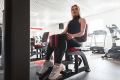 Beautiful young woman in black sportswear in gym shoes is sitting on a modern simulator in the gym. Girl shakes her buttocks royalty free stock images