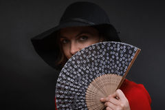 The beautiful young woman in a black wide-brimmed hat and dress of scarlet color with fan in hand. The beautiful young woman in a black wide-brimmed hat and a stock images
