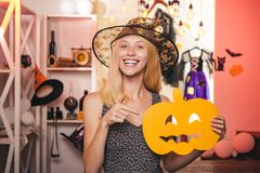 Beautiful young woman in black witch costume with hat and broom standing over pink background. Wide Halloween party art stock photography