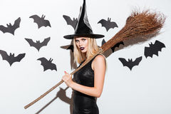 Beautiful young woman in black witch halloween costume with broom Royalty Free Stock Images