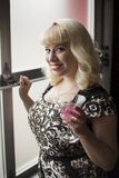 Beautiful Young Woman with Blond Hair Drinking a Pink Martini Royalty Free Stock Image