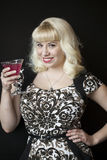 Beautiful Young Woman with Blond Hair Drinking a Pink Martini Royalty Free Stock Images