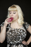 Beautiful Young Woman with Blond Hair Drinking a Pink Martini Stock Photo