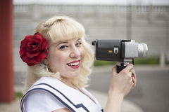 Beautiful Young Woman with Blond Hair and Movie Camera Royalty Free Stock Photography