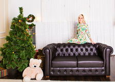 Beautiful young woman with blond hair posing beside Christmas tree and presents Stock Images