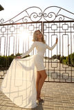 Beautiful young woman with blond hair wears elegant white dress Royalty Free Stock Photo