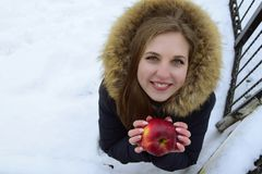 The beautiful young woman the blonde with blue eyes holds red apple in hand. The woman is dressed in a hood with fur. The woman is against the background of Royalty Free Stock Photo
