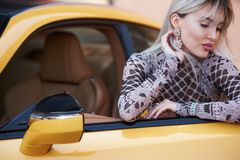 Beautiful young woman standing near beautiful yellow sports car. Beautiful young woman with blonde hair, and red lipstick, standing near beautiful yellow sports Royalty Free Stock Photos