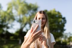 Beautiful young woman with blonde hair using mobile phone outdoor. Stylish girl making selfie stock photography