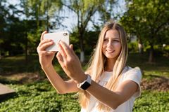 Beautiful young woman with blonde hair using mobile phone outdoor. Stylish girl making selfie royalty free stock photo