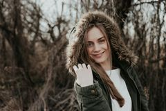 Smiling woman posing on camera in jacket with fur hood. Beautiful young woman with blonde hair, wide eyebrows and blue eyes looking at camera. Girl posing at Royalty Free Stock Photography