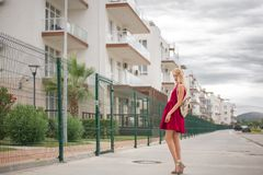 Beautiful young woman blonde with long hair in a fashionable burgundy dress royalty free stock photography