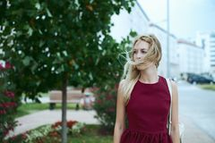 Beautiful young woman blonde with long hair in a fashionable burgundy dress stock image