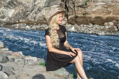 A beautiful young woman blonde with long hair in a hat sitting on a rocky shore by the river. Around the mountains royalty free stock images