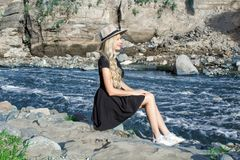 A beautiful young woman blonde with long hair in a hat sitting on a rocky shore by the river. Around the mountains stock photography