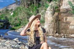 A beautiful young woman blonde with long hair in a hat sitting on a rocky shore by the river. Around the mountains and rocky terra royalty free stock photos