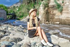 A beautiful young woman blonde with long hair in a hat sitting on a rocky shore by the river. Around the mountains and rocky terra royalty free stock photo