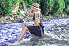 A beautiful young woman blonde with long hair in a hat sitting on a rocky shore by the river. Around the mountains stock images